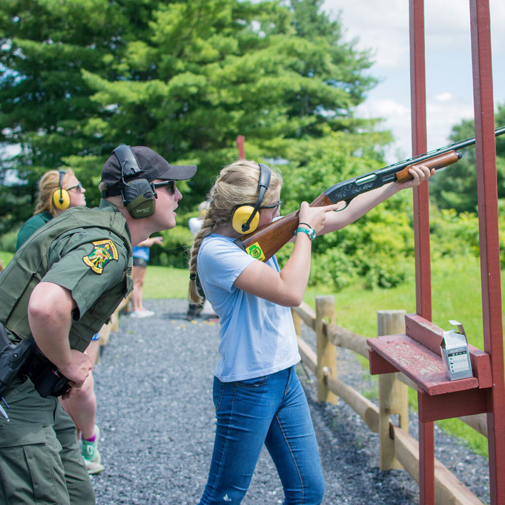A child firing a shotgun under supervision from a Vermont game warden