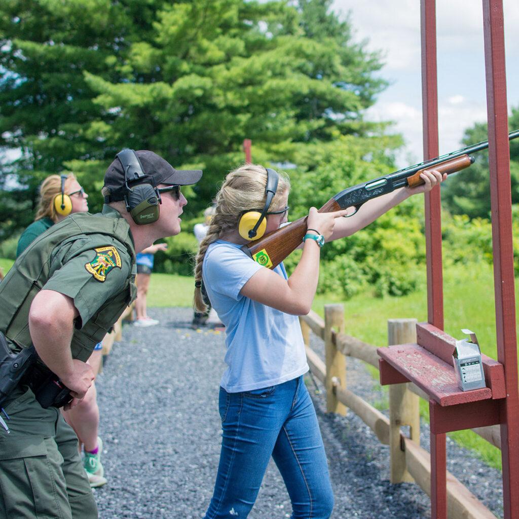 A child firing a shotgun under supervision from a Vermont game warden