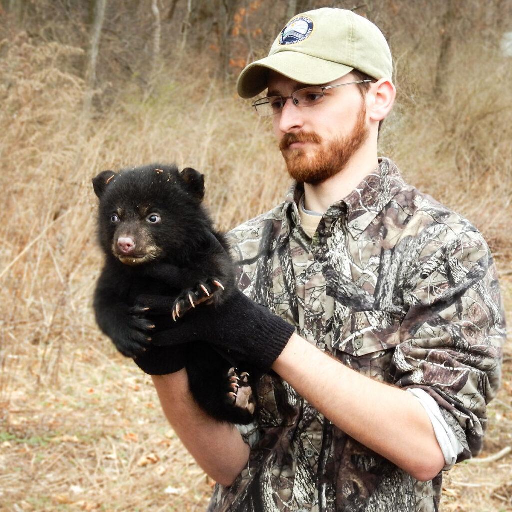 Biologist with a bear cub