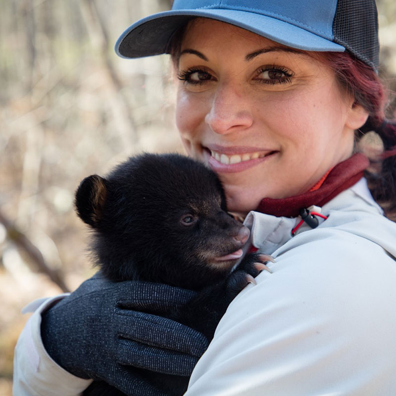 A woman holding a bear cub