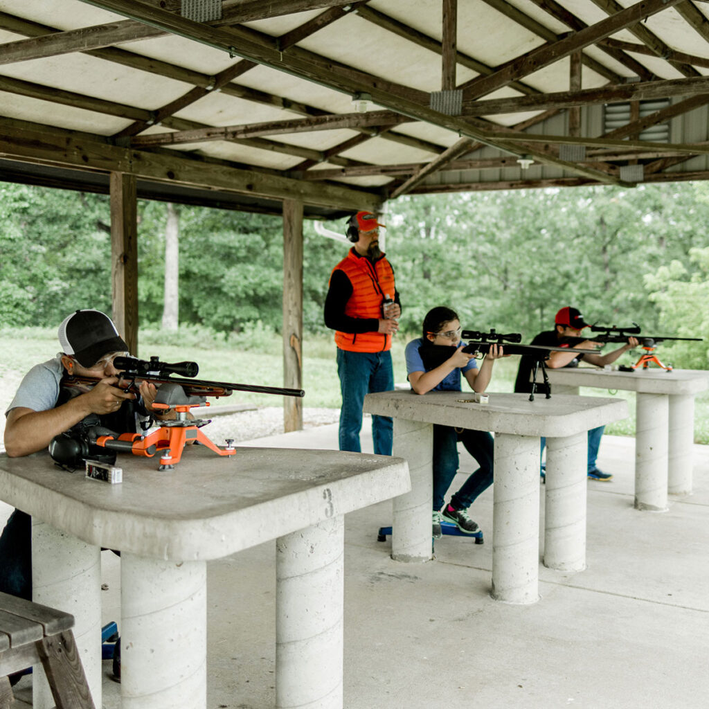 Three people aiming rifles under supervision of an instructor at a target range