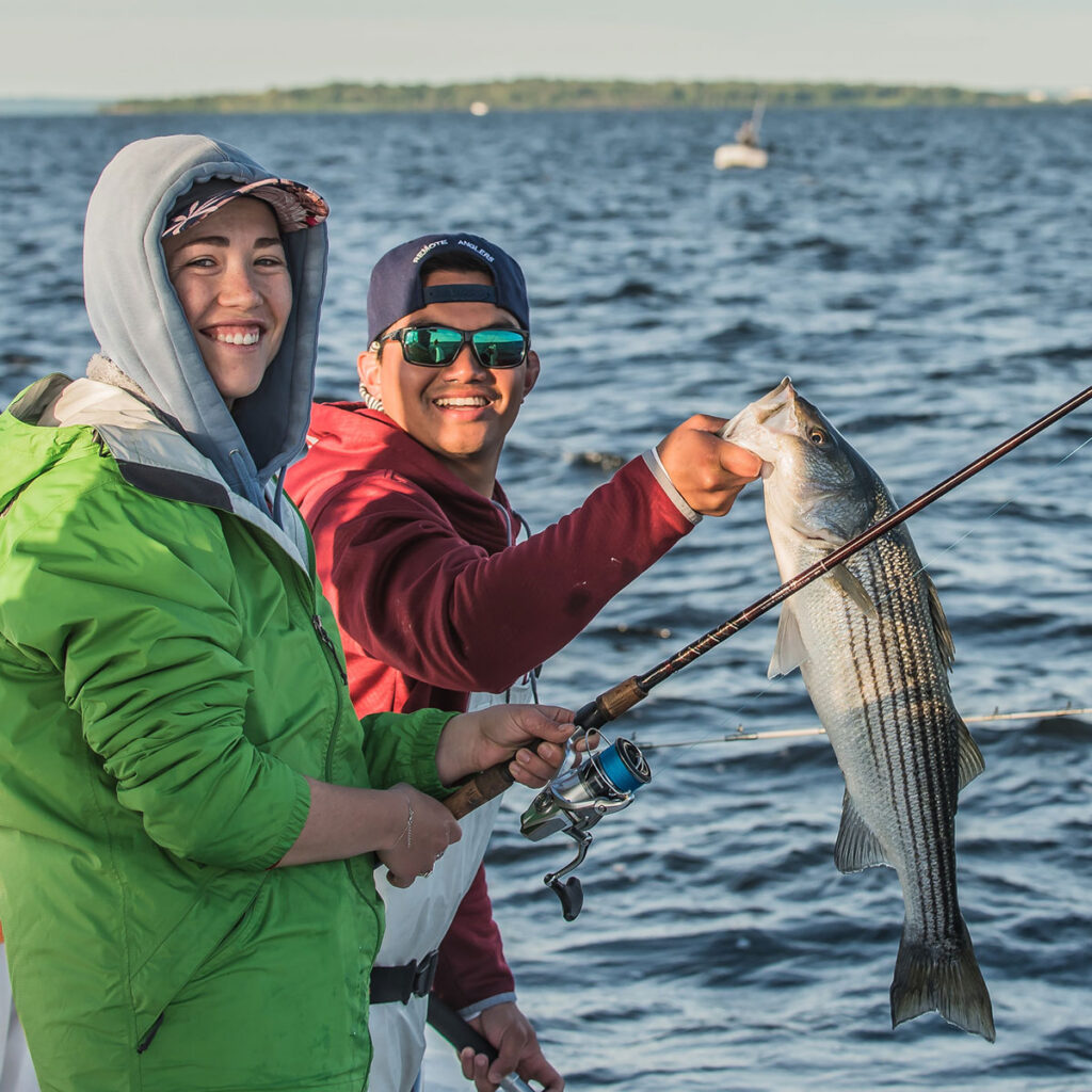 Two young adults on a boat with a striped bass