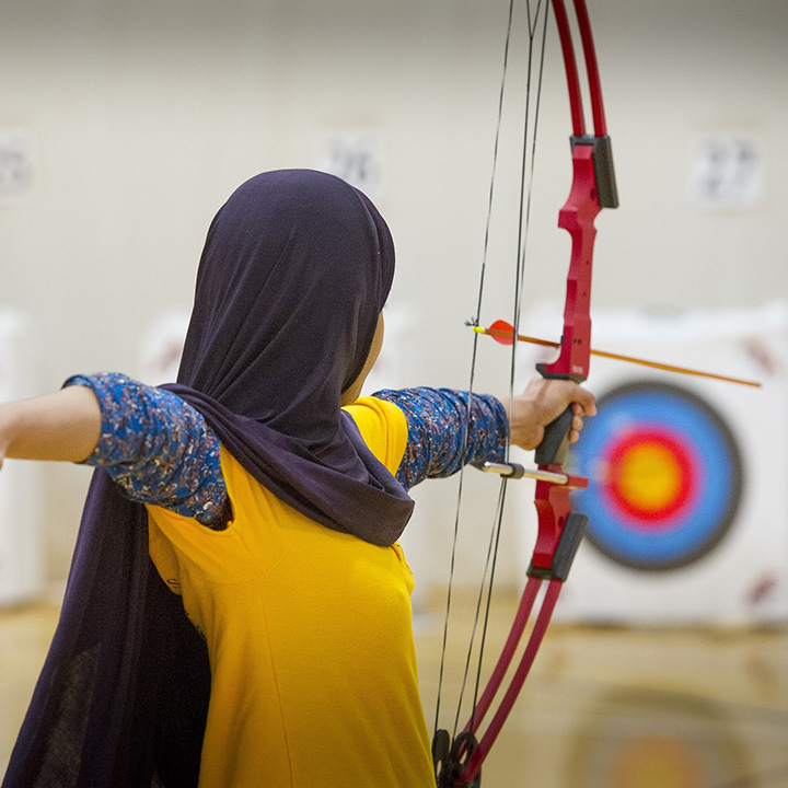 A girl in hijab shooting a bow