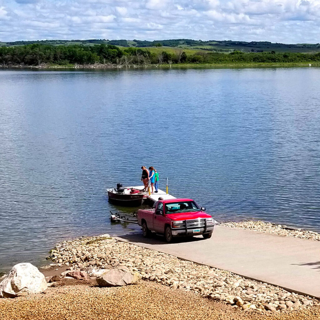 Three people launching a boat at a boat ramp