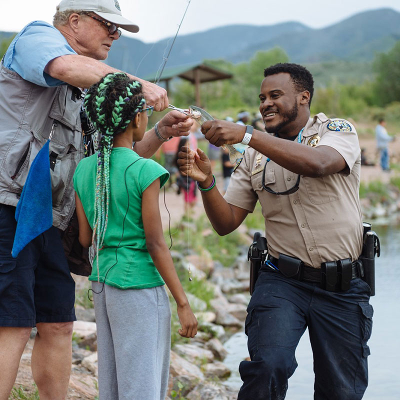 A Colorado Parks and Wildlife employee helping people unhook a fish