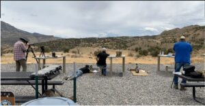 Three people at a target range outdoors