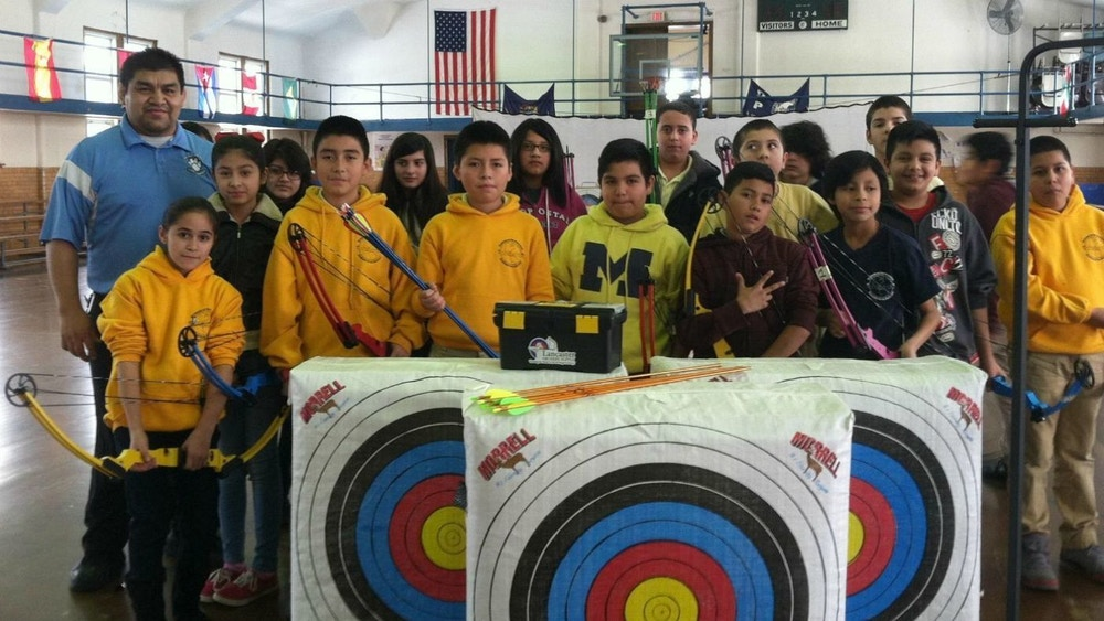 Group of youth archers in a school gymnasium