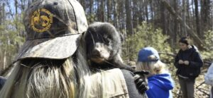 Person with a wildife and sport fish restoration hat holding a bear cub over their shoulder